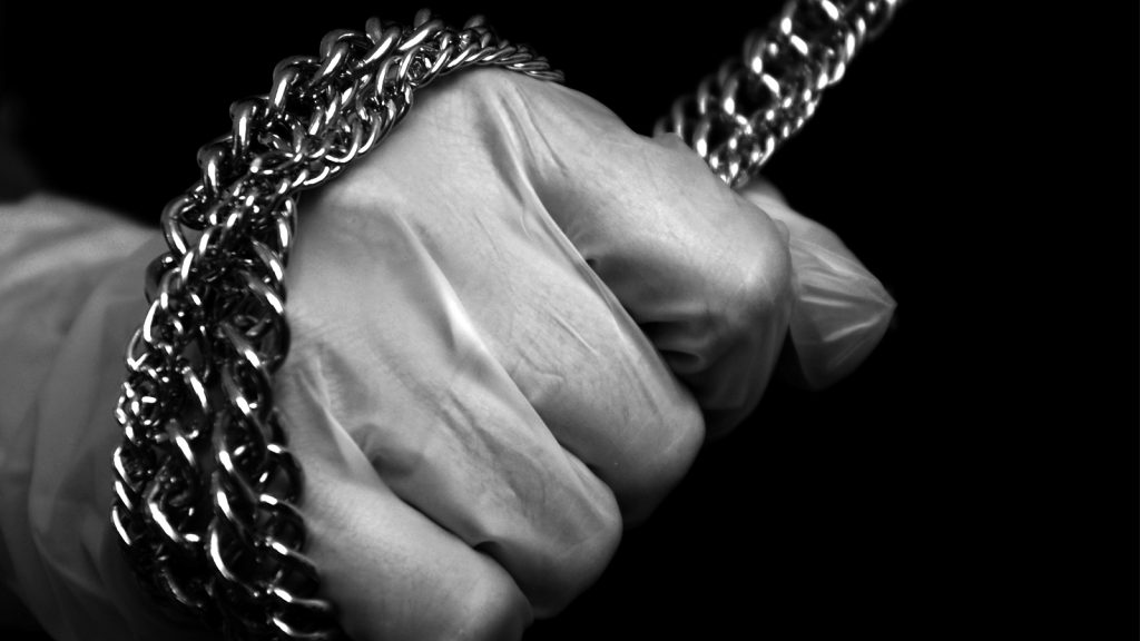 Black and white photograph of a hand holding onto a chain.