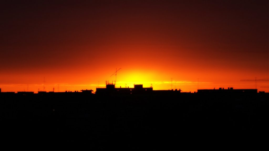 Color photograph of a deep orange and red sunset over an urban cityscape.