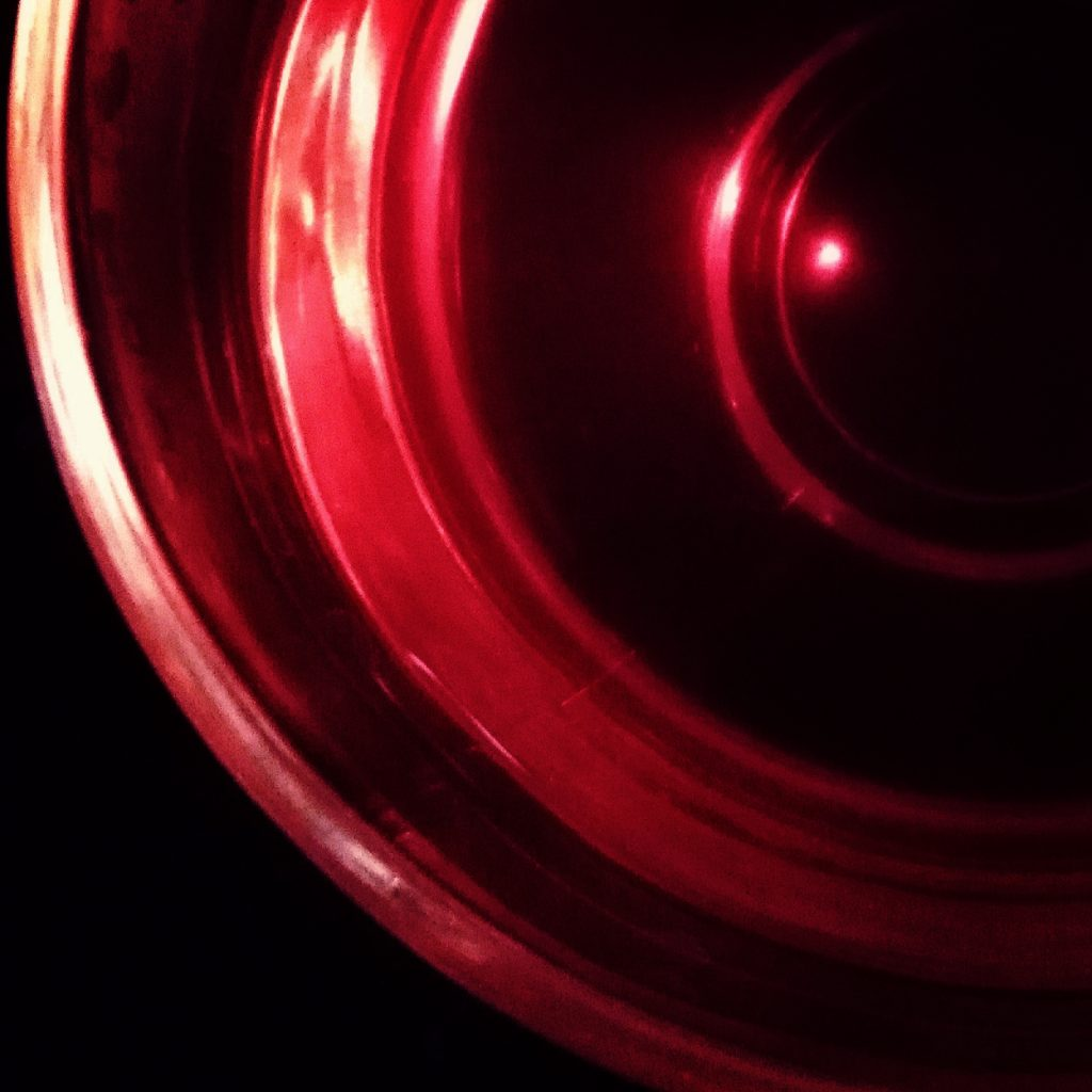 Image in dark red and black of concentric circles with a brighter spot in the middle.